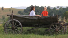 Beautiful mother and lovely son relaxing on wooden cart Stock Footage