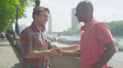4k Happy mixed ethnicity male friends meet up in the city Stock Footage