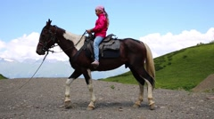 Happy girl learns to control of horse among mountains at summer Stock Footage