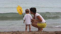 Young mother and baby child on seashore playing with a hand mill, summer holiday - stock footage
