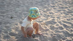 Baby child seating at seashore ang playing with the sand Stock Footage