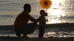 Father and baby son playing with hand mill at the seashore, sunrise time Stock Footage