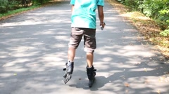 Back of boy with toys in shorts roller skating in summer park Stock Footage