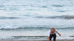 Baby child shoesless playing with sand at seaside, sea waving Stock Footage