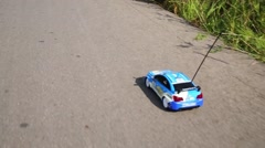 Radio controlled toy car moves on road at summer day. Stock Footage