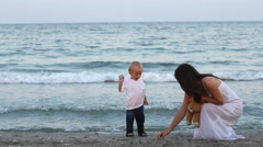 Mother and baby son at seaside woman search sea shell baby throwing shell in sea Stock Footage