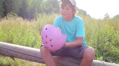 Boy with pink helmet and roller skates sits on log Stock Footage