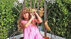 Pretty girl in pink dress tries on crown in summer park in city Stock Footage