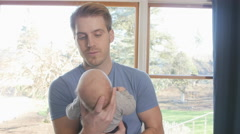 Father making faces at newborn son Stock Footage