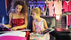 Young mother with daughter see catalogs on couch in clothes shop - stock footage