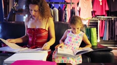Young mother with daughter see catalogs in clothes shop - stock footage