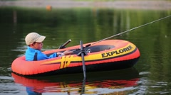 Boy (model with release) paddles in inflatable boat Intex Explorer Stock Footage