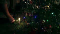 Man Hand Lighting Traditional Candle Light Decoration of Real Christmas Tree - stock footage