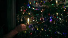 Man Hand Lighting Traditional Candle Light Decoration of Real Christmas Tree Stock Footage