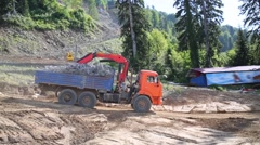 Moving orange truck with loading crane on construction site Stock Footage