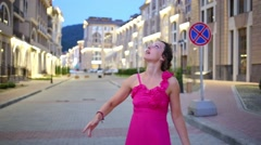 Pretty woman in dress haves fun on street at summer evening Stock Footage