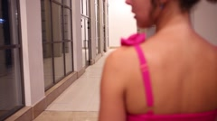 Back of woman in pink dress going in white corridor Stock Footage