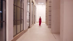 Beautiful woman in pink dress going in white corridor Stock Footage