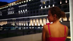 Back of woman in pink dress looking at building with illumination Stock Footage
