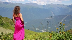 Pretty woman in dress looks at beautiful mountains, turns and smiles Arkistovideo