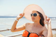Beautiful young pretty woman in sunglasses and white hat by the sea Kuvituskuvat