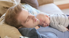 Father and newborn son asleep on couch - stock footage