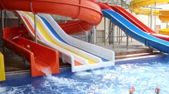 Happy girl moves on slide and boy in water looks at she in pool Stock Footage