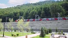 Modern high-speed train moves near mountain art summer Stock Footage