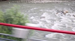 Small water stream among stones. View from moving train Stock Footage