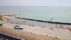 Sea with resting people and parked cars at summer day. Stock Footage