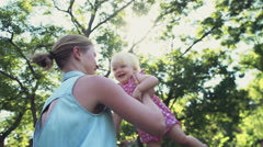 Mother spinning with her child in the park slow motion Stock Footage