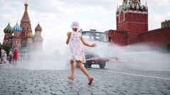 Stock Video Footage of Girl in dress run in front watering truck on Red square in Moscow