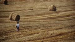 Boy going on the field, around the haystacks mown field, sunny day Stock Footage