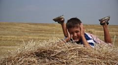 Boy lying on a hay looking at the camera smiling and waving legs Stock Footage