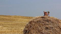 Boy in a hat lying on haystack looking into the camera smiles and waves legs Stock Footage