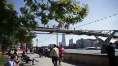 Runners by Millennium Bridge and Tate Modern pan, London Stock Footage