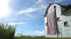 Barn and flag low side shot morning Stock Footage
