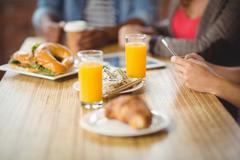 Cropped image of woman using phone during breakfast - stock photo