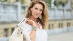 Attractive woman in town holding purse - stock footage