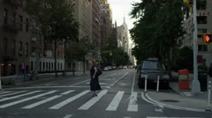 Stock Video Footage of woman crossing street empty morning Lower 5th Ave Empire State Building NYC 4K