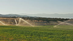 Morning sun lights sprinklers in mountain field cedar hills mountains background Stock Footage