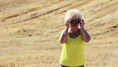 woman wears glasses and looking into the camera, farmer on the field - stock footage