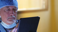 Male surgeon using ipad/tablet - stock footage