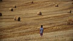 Boy is on the field, around the haystacks mown field, sunny day Stock Footage