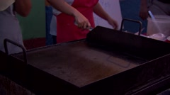 Women make crepes at street stall Stock Footage