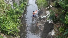 2 boys mining a polluted river Stock Footage