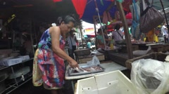 Vendor de-scaling fish at sidewalk Stock Footage