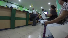 People seated in queue in government office Stock Footage