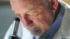 Man in a lab coat using a microscope Stock Footage