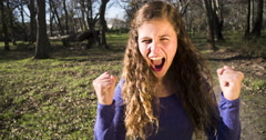 Excited young beauty in woodland setting cheers someone on in slow motion. Stock Footage